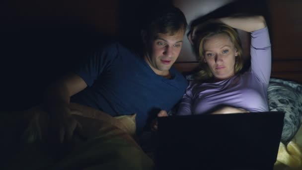 Couple, man and woman, watching a movie on a laptop on a bed in ...